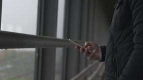 Close-up of a man using smart phone at a footbrigde. Close-up of a man standing on a footbridge a gray and cloudy day using a smart phone stock video footage