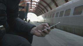Close-up of a man using smart phone at train station. Close-up of a man sitting at a train station hall, using a smart phone stock video footage