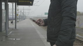 Close-up of a man using smart phone at train station. Close-up of a man standing at a train station, a gray and cloudy day using a smart phone stock video footage