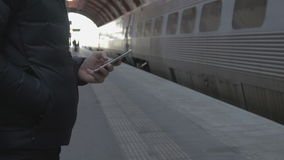 Close-up of a man using smart phone at train station. Close-up of a man standing at a train station hall, using a smart phone stock video