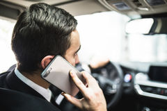 Close up of man using smartphone while driving car Royalty Free Stock Image
