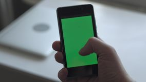 Man using smartphone. Close up - Man using smartphone with green screen in home stock video footage