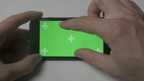 Close up man using smartphone touch with green screen chroma key on white desk background. Close up man holding smartphone touch with green screen stock video