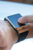 Close-up of man using smartwatch app with finger Stock Image