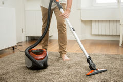 Close up of man vacuum cleaning the carpet Royalty Free Stock Images