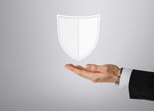 Close up of man with virtual antivirus shield icon. Business, people and cyber protection concept - close up of male hand with virtual antivirus program shield Stock Photos