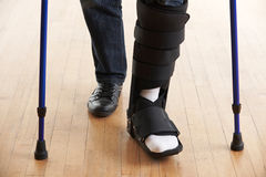 Close Up Of Man Walking With Crutches And Cast Stock Photo