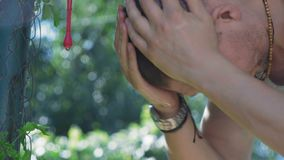 Close-up of a Man Washing His Face from the Village Washbasin of the Hanging Fence in the Village stock footage