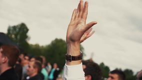 Close up of man waving hand in park on summer festival among other people. stock video footage