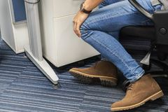 Man wearing jeans and boot shoes sit on office chair royalty free stock photos