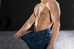 Close-up Of A Man Wearing Loose Jean. Showing Weight Loss In The Gym Stock Image