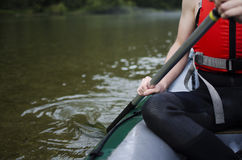 Close up of a man wearing safety vest and holding paddle on boat. Summer sport activities Stock Image