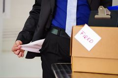 Close up of man wearing a suit holding his empty pockets with a box of his belongings after being fired from his job in. A blurred background Royalty Free Stock Photo