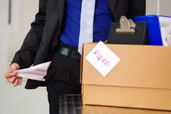 Close up of man wearing a suit holding his empty pockets with a box of his belongings after being fired from his job in. A blurred background Stock Images