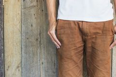 Close up man wearing a white shirt, brown pants standing at wood wall background with copy space. Hipster, Vintage, minimal style Stock Image