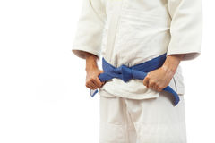 Close-up of a man  in a white kimono for judo, ties up a blue be. Close-up of a man fighter in a white kimono for judo, Jiu Jitsu ties up a blue belt on an Royalty Free Stock Photo