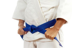 Close-up of a man  in a white kimono for judo, ties up a blue be. Close-up of a male fighter in a white kimono for judo, Jiu Jitsu ties a blue belt on an Royalty Free Stock Image