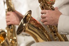 Close-up. A man in a white suit plays a saxophone in a jazz orchestra. Shallow depth of field. Close-up. A man in a white suit plays a saxophone in a jazz Royalty Free Stock Images