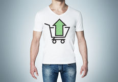Close-up of a man in a white t-shirt with a sketch of the green arrow and the basket. A concept of the increasing of the purchasing power Stock Photos