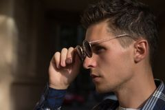 close-up of a man who takes off his sunglasses,male portrait in profile, where he holds glasses, touches glasses.buying points royalty free stock image