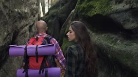 Close-up. Man and woman with a backpack walking along the path of a pedestrian path between the rocks during the sunny. Sunny autumn day slow motion stock footage