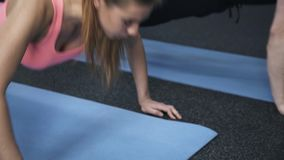 Close up of man and woman doing pushups in a gym stock footage
