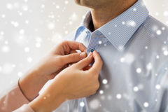 Close up of man and woman fastening shirt button Royalty Free Stock Photography