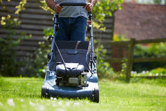 Close Up Of Man Working In Garden Cutting Grass With Mower Royalty Free Stock Image