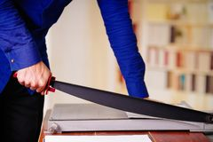Close up of man working on the guillotine, cutting paper.  Royalty Free Stock Image