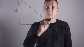 Close-up of a man writing formulas on a glass whiteboard stock video
