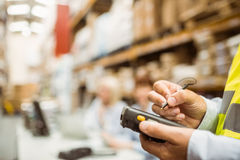 Close up of manager wearing yellow vest using handheld. In a large warehouse Stock Photography