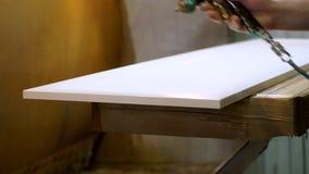 Close-up Manchando a madeira com arma de pulverizador Pintor que usa o aer?grafo para pintar filme