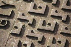 Close up of a manhole cover with `G` and `S` pattern stock images