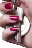 Close up of manicured fingers. Painted a deep glossy red curling around set of car keys royalty free stock image