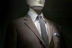Brown Checkered Jacket, White Shirt, Grey Tie And Striped Handke. Close-up of a mannequin in a brown checkered jacket with white shirt, grey tie and striped blue royalty free stock image