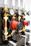Close up of manometer, pipe, flow meter, water pumps and valves of heating system in a boiler room.  stock images