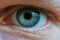 Close up of a mans blue eyes, extrem macro. Reflection of a buildingin the eye. Stock Photo