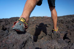 Close-up of mans feet walking on lava field. Close-up of man's feet walking on lava field in sport shoes. Canary Islands, Lanzarote, Timanfaya National Park royalty free stock images