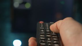 Close up man hand holding the TV remote control and changing channels. Close up mans hand holding TV remote control and changing TV channels. Blurry background stock footage