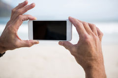 Close-up of mans hand taking picture on mobile phone on beach Stock Photo
