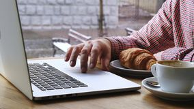Close-up of mans hand using notebook.On the table are coffee and croissant. Close-up of mans hand using notebook. On the table are coffee and croissant stock video