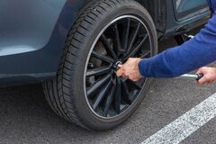 Free Close Up Mans Hands Changing A Wheel Using Screwdriver. Replacing Winter And Summer Tires. Seasonal Tire Replacement Concept. Stock Photo - 175455660