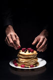 Close up of mans hands decorating the pancakes Royalty Free Stock Photo