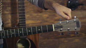 Close up mans hands tuning an acoustic guitar slow motion stock video footage