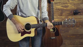 Close up mans hands tuning an acoustic guitar slow motion stock video