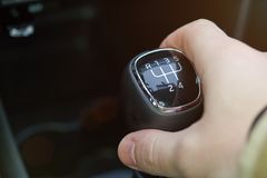 Close up of manual gear stick in hand. Changing gear theme Stock Photo