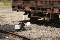 Close-up of a manual operated siding and an old train wagon. A close-up of an old and manual operated siding of a railroad track. Behind the siding is an old royalty free stock photography