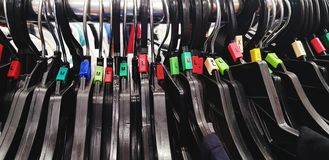 Close up many black plastic clothing hanger with different size. S, M, L, XL, and 2XL at shopping store Royalty Free Stock Image