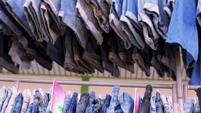 Close up of many blue jeans hanging on a rail. stock video