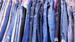 Close up of many blue jeans hanging on a rail. stock footage